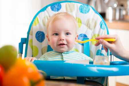 mom feeds funny baby with spoon Stock Photo