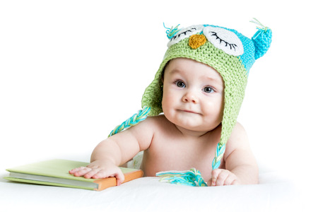 baby in funny owl knitted  hat owl with book  on white background photo