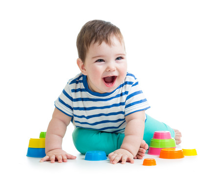 developmental: cheerful child playing with colorful toy isolated on white