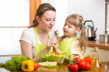 mother feeding kid vegetables in kitchen photo
