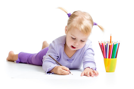 Cute kid drawing with color pencils photo