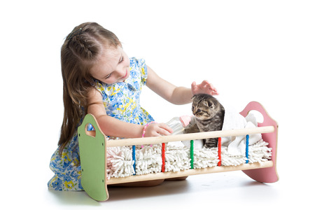 child girl feeding and playing kitten cat photo