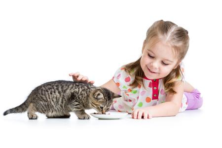 cute kid girl feeding kitten photo
