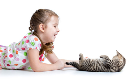 happy kid lying on floor and playing with cat kitten photo