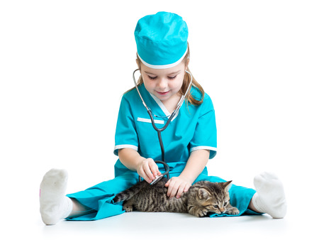 Child girl playing doctor with cat kitten photo