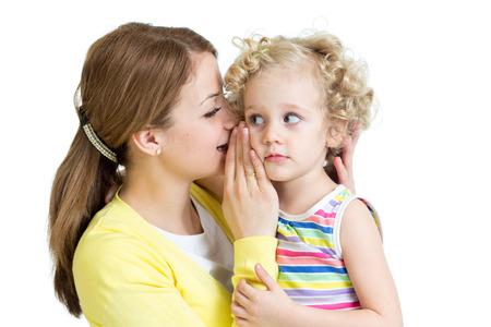 niños platicando: madre e hija comparten un susurro secreto Foto de archivo