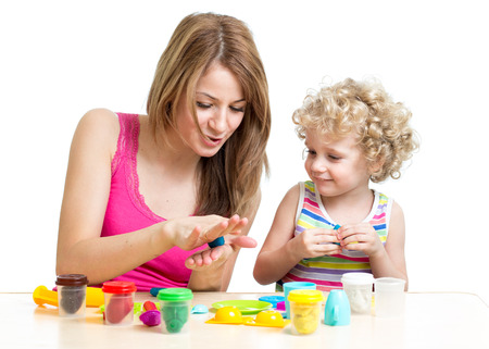 clay craft: child and mother play colorful clay toy Stock Photo