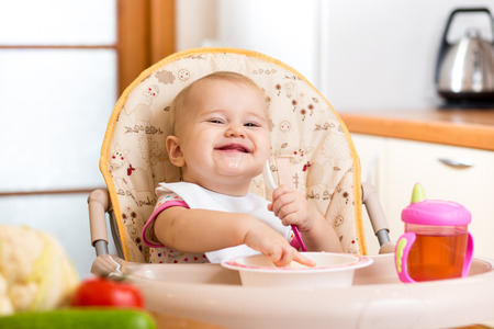 smiling baby eating healthy food on kitchen