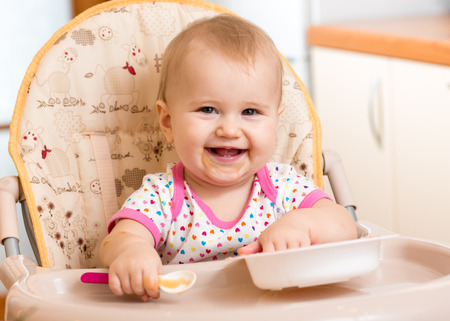 baby eating: smiling baby eating food on kitchen Stock Photo