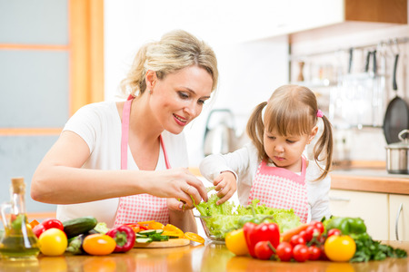 mother teaching kid daughter mixing salad at kitchen Banco de Imagens