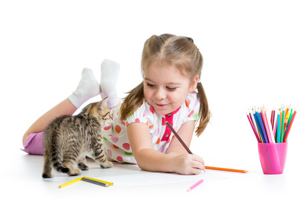 child drawing with pencils and playing with kitten photo