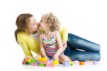 cheerful mother and kid play with toys on floor photo