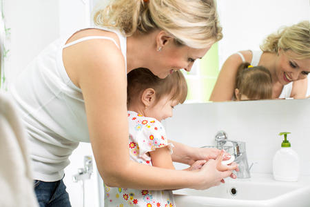 mother washing baby hands photo