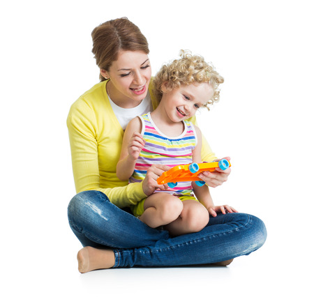 Mother and kid girl having fun with musical toy. Isolated on white background photo