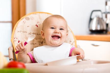 Lachende baby het eten van gezond voedsel op keuken Stockfoto - 25719804