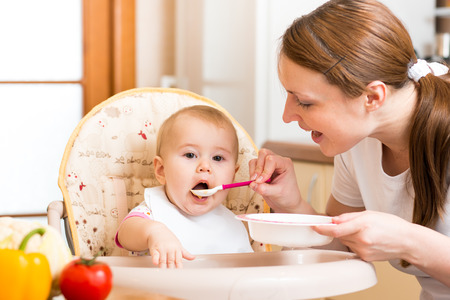 infant hand: Mom feeds baby with spoon