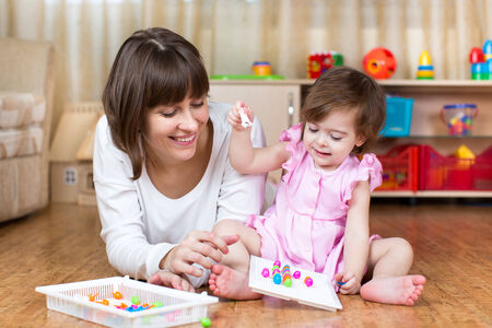 children playing with toys: mother and kid play together in home interior Stock Photo