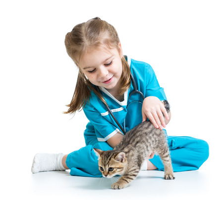 Kid girl playing doctor with cat kitten photo
