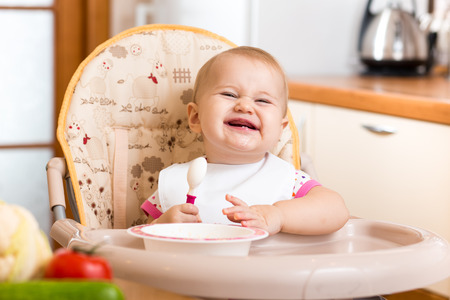 baby chair: funny baby eating healthy food on kitchen Stock Photo