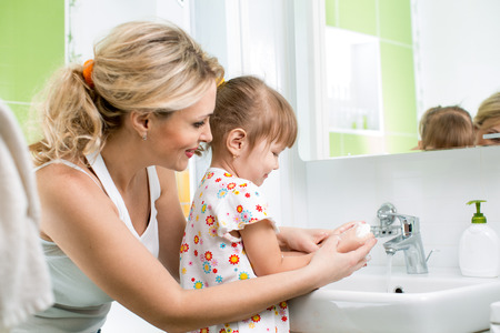 kid washing hands with mom