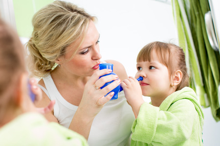 watering pot: mother and kid with neti pot ready for nasal irrigation or douche Stock Photo