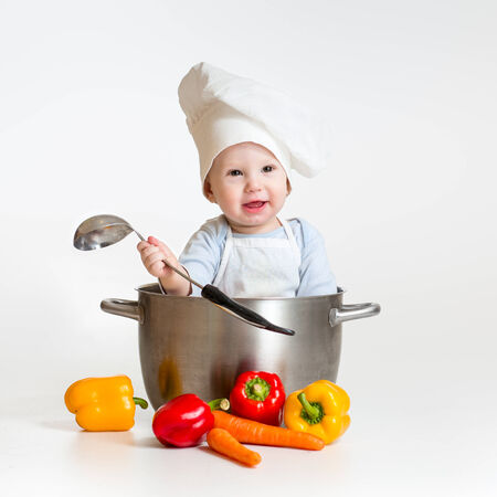 cook baby sitting inside pan with healthy food photo