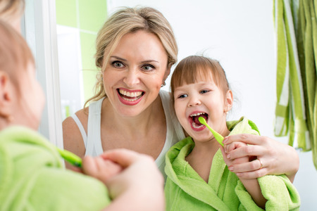 mother with kid brushing teeth photo