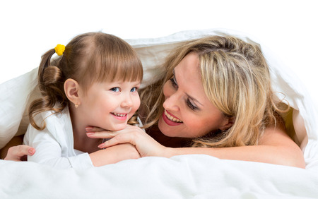 smiling mother and kid lying under the blanket photo