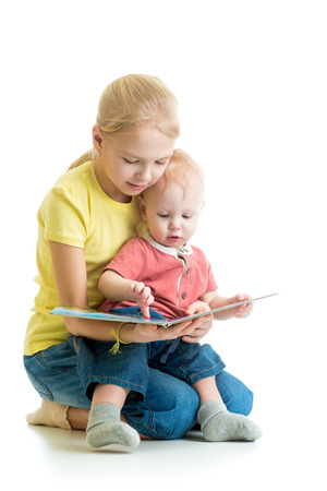 kid girl playing reading book to her little brother photo