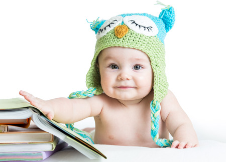 baby in funny owl knitted  hat owl with books  on white
