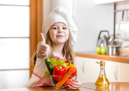 kid girl weared as cook with vegetables at kitchen photo