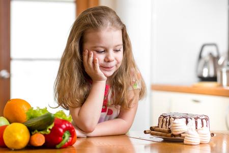 chico de elegir entre vegetales saludables y sabrosos dulces