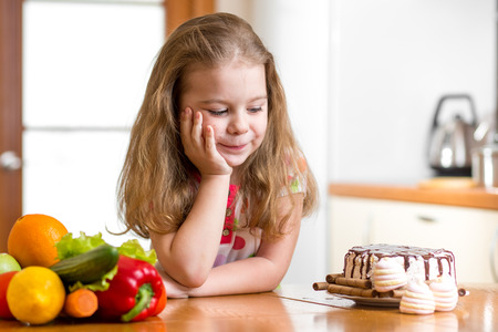 kid choosing between healthy vegetables and tasty sweets Фото со стока - 26068071