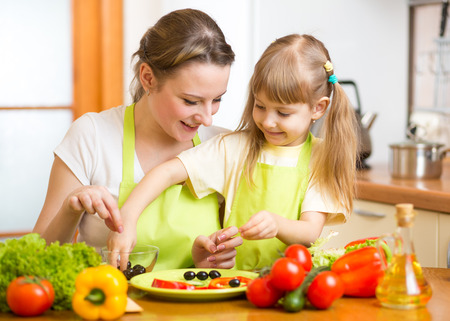 mother and kid daughter cooking in the kitchen photo