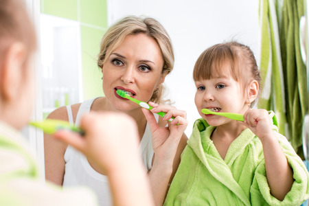 routines: mother with child brushing teeth Stock Photo