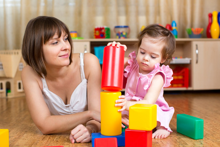 tower block: mom and child play block toys indoors