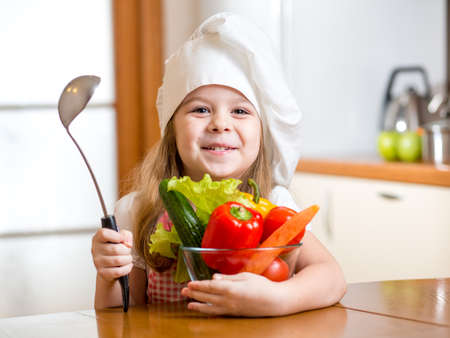 child girl weared as cook with vegetables at kitchen photo