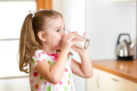 chica niño beber de yogur o leche en la cocina