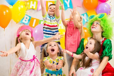 globos de cumpleaños: grupo de niños con la fiesta de cumpleaños que celebra payaso Foto de archivo