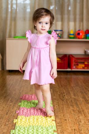 pied fille: enfant à lui masser les pieds sur le tapis médicale Banque d'images