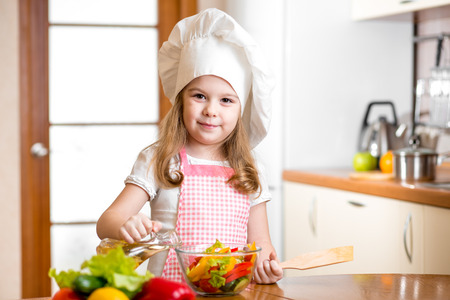 child girl cooking at kitchen photo