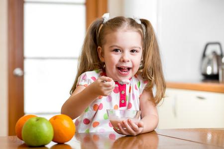 yogur: niño comer alimentos saludables en la cocina
