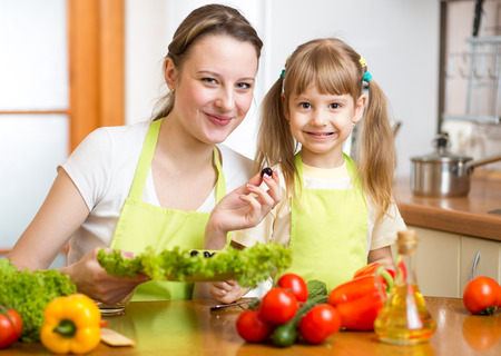 Young mother and her kid making vegetable salad photo
