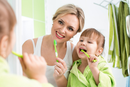 tooth cleaning: mother and child daughter brushing teeth in bathroom