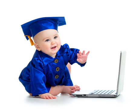 happy child in academician clothes  using laptop photo