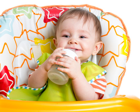 highchair: smiling baby drinking from bottle sitting in high chair