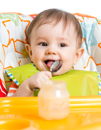 smiling baby eating food with spoon photo
