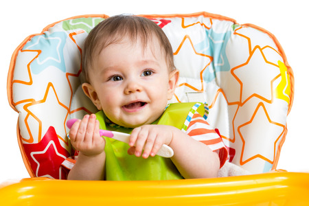 highchair: smiling baby boy with spoon Stock Photo