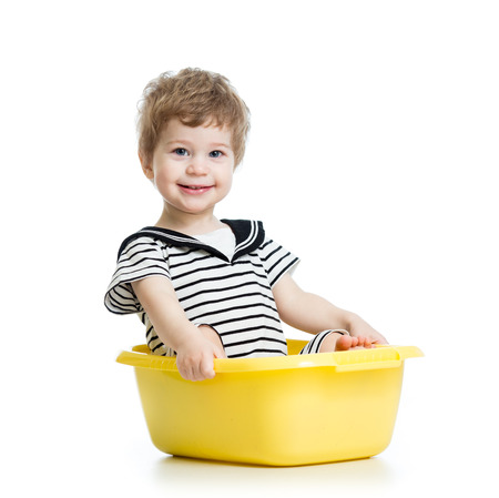 smiling kid weared sailor clothes and  sitting inside washbowl photo
