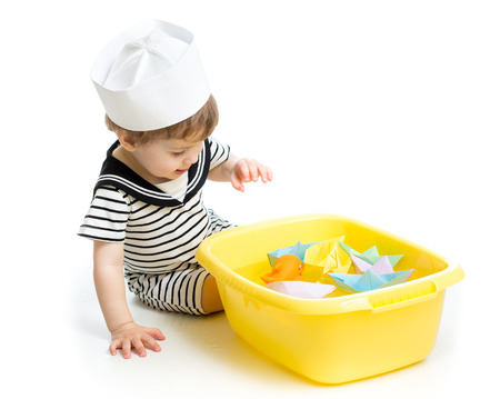 Cute baby boy with sailor hat  playing with paper boats photo